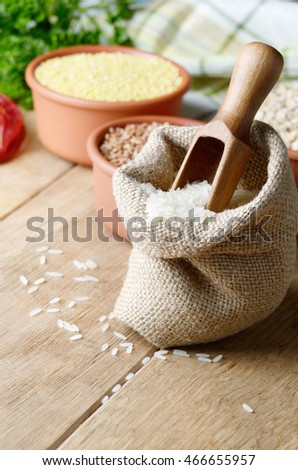Organic rice grains in burlap sack on kitchen table