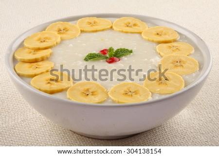 Organic rice pudding with cream and bananas. - stock photo