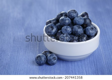 organic ripe blueberries in bowl, on wood table