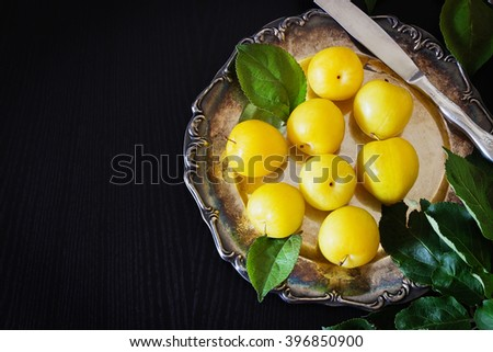Organic ripe yellow plums in vintage metal plate on a black wooden background. Bio healthy food. View from above. Copy space background - stock photo