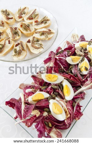 Organic Salad and snacks; Hard-boiled eggs with organic red chicory, snack canape selection with fish fillets, Mediterranean Sea fennel, dried tomato, capers; selective focus