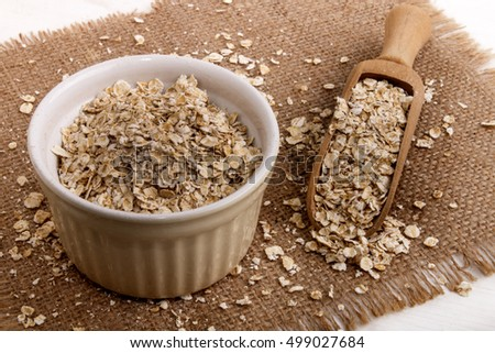 organic scottish toasted oats in a bowl, wooden scoop and brown jute