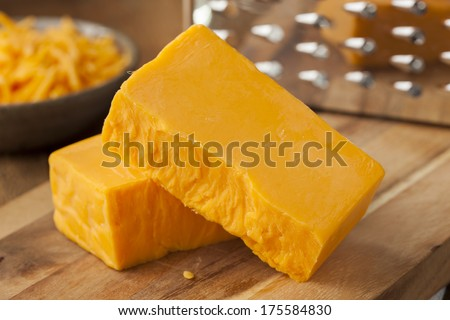 Organic Sharp Cheddar Cheese on a Cutting Board - stock photo