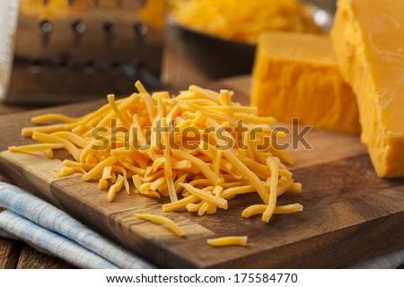Organic Shredded Sharp Cheddar Cheese on a Cutting Board - stock photo