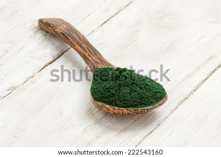 Organic spirulina algae powder in wooden spoon - stock photo