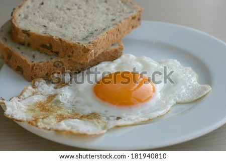 Organic sunny side up egg with whole wheat toast served on a plate on a kitchen table - stock photo
