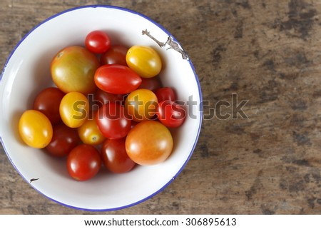 organic tomatoes, organic colorful tomatoes, colorful tomato in galvanized bowl with rural atmosphere. colorful tomato in galvanized bowl on old wood background. fresh tomatoes.