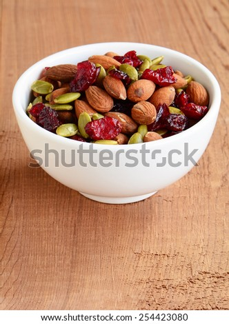 Organic trail mix of roasted almonds, raw pumpkin seeds (pepitas) and dried cranberries for a healthy snack - stock photo