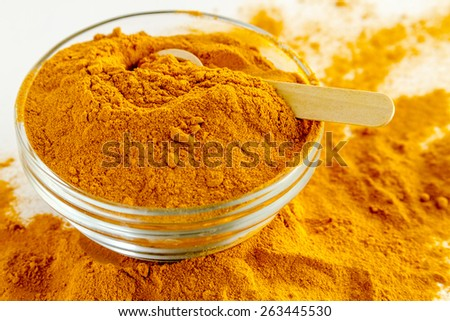 Organic turmeric (curcuma) powder in glass bowl with measuring spoon on white background - stock photo