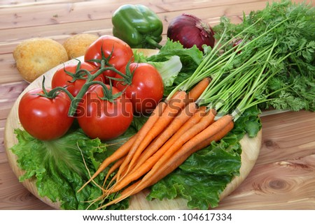 Organic vegetables in rustic setting including tomatoes on the vine, peppers, carrots, lettuce and dinner rolls - stock photo