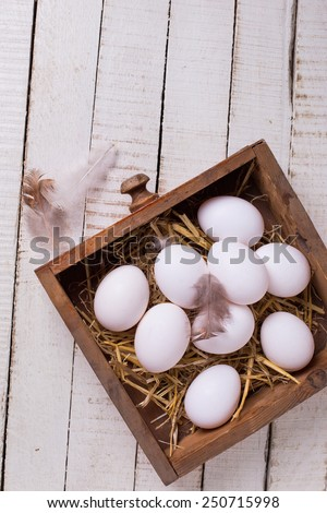 Organic white eggs in box on white wooden painted planks. Selective focus.  - stock photo