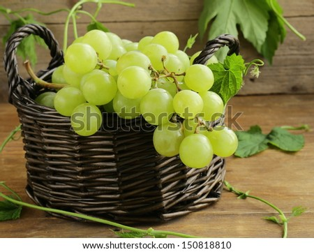Organic white grapes in a basket on a wooden table - stock photo