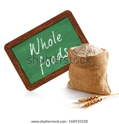 Organic whole flour in sack with whole foods chalkboard sign on white background - stock photo