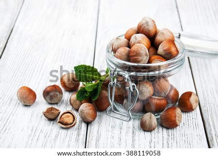 organic whole hazelnuts in a glass jar on a old wooden table