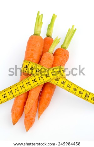 organically grown carrots with tape measure. fresh fruit and vegetables is always healthy. symbolic photo for healthy diet - stock photo