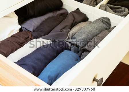 organised wardrobe, rolling shirts is the trick - stock photo