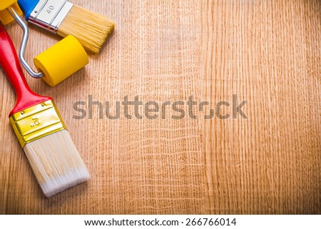 organized copyspace two paint brushes and roller on wooden board  - stock photo