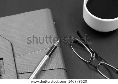Organizer on table with pen and glasses - stock photo