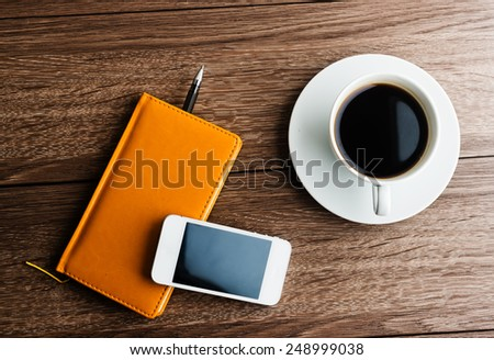 organizer with cup of coffee and mobile phone on desk - stock photo