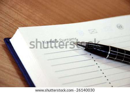 organizer with metallic black pen on desk - stock photo
