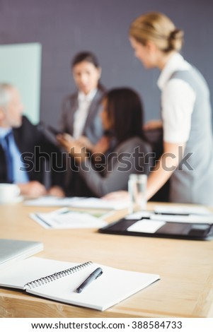 Organizer with pen on table in conference room and businesspeople interacting in background