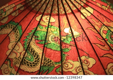 Oriental bamboo & paper umbrella with dragon painting, close-up: Dragon - the symbol of POWER for Chinese & Japanese - stock photo