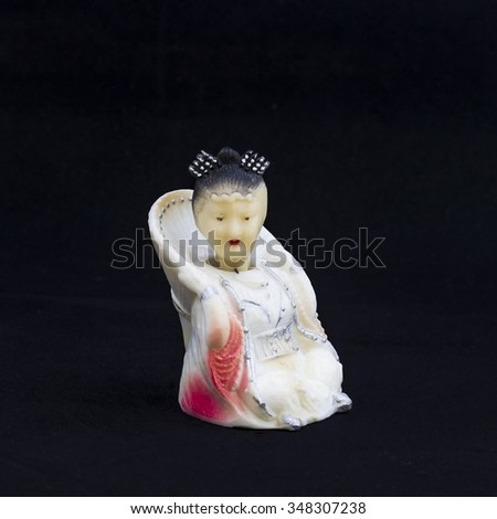 Oriental beauty - antique figurine from bone. Background is black.