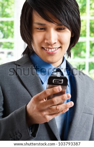 Oriental businessman reading an email on his smartphone