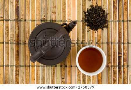 Oriental Clay Teapot with Cup of Brewed Tea & Loose Tea leaves on BAmboo Background - stock photo