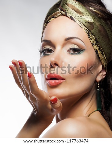 Oriental fashion style. Beautiful lady magic face. Glamor. Blowing a kiss - stock photo