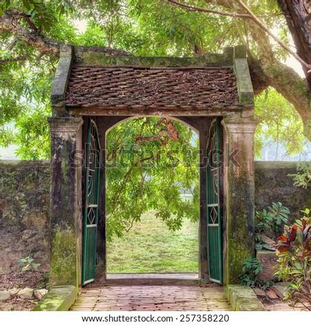 oriental gate in the tropical asian garden, Ninh Binh province, Vietnam - stock photo