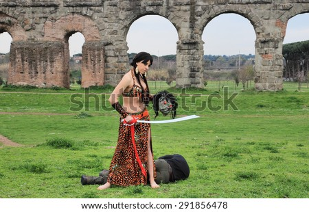 oriental odalisque with sword and dead decapitated monster - stock photo