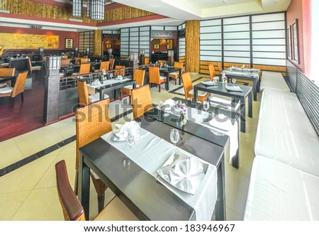 Oriental style interior of the japanese restaurant with nicely served table with napkins of the luxury five stars resort, hotel. Interior design.