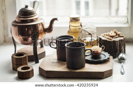 Oriental style tea serving with brown sugar, honey and herbal infusions in the bottles. Wooden board, white rustic table.