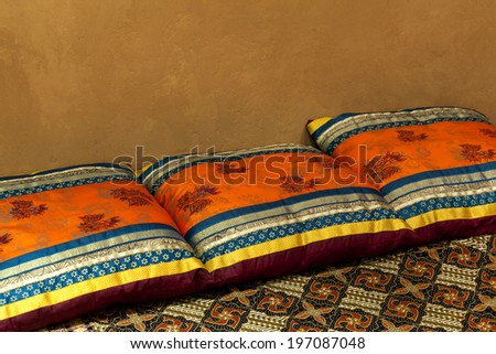 Oriental styled cushions on bed - stock photo