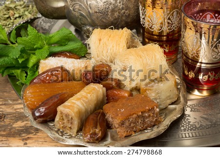 Oriental sweet cookies, tea cups and mint leaves on a Moroccan tea tray - stock photo