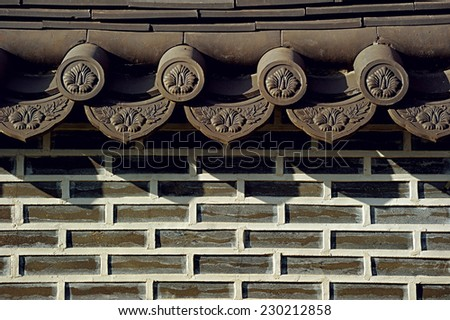 Oriental Wall; a brick wall in oriental style with roof element on top - stock photo