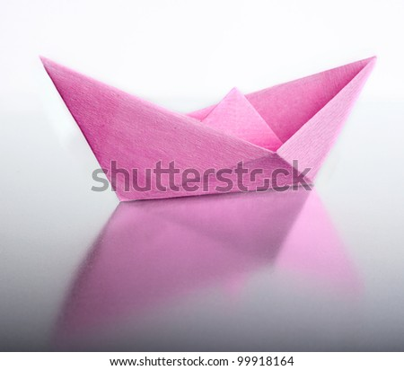 Origami a boat from the pink paper. - stock photo