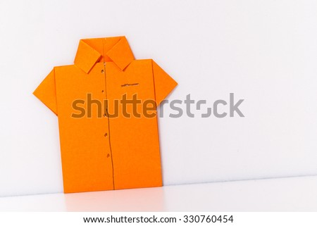origami a man's shirt on a white background orange of paper - stock photo
