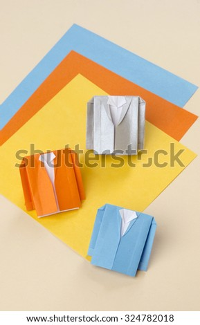 origami a man's suit jacket with a shirt on a bright yellow background orange blue sheets of paper - stock photo