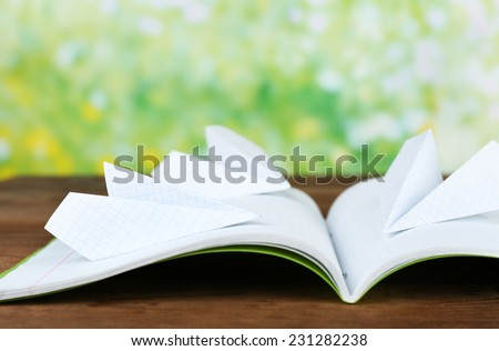 Origami airplanes on notebook, on wooden table, outdoors - stock photo