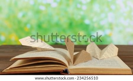 Origami airplanes on old book, on wooden table, outdoors - stock photo