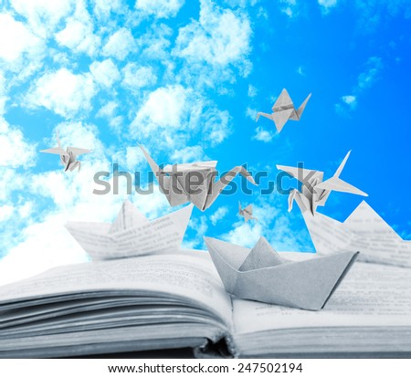 Origami boats and cranes on book on sky background - stock photo