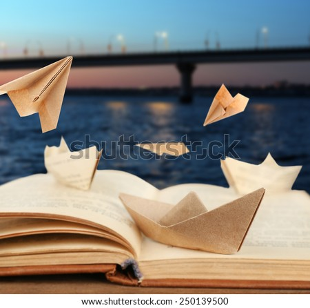 Origami boats on old book on bridge background - stock photo