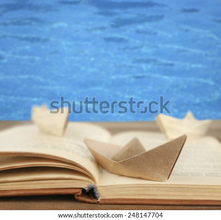 Origami boats on old book on sea background - stock photo