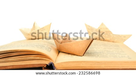 Origami boats on old book, on white background - stock photo