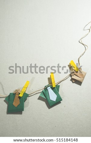 Origami clothes on laundry. Paper background