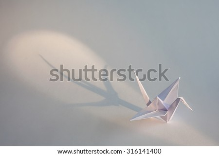 Origami crane isolated on white background with shadow. - stock photo