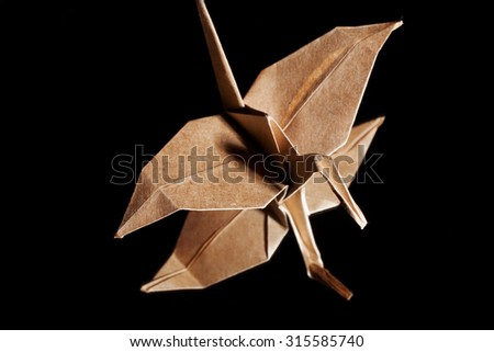 Origami crane made from brown recycle paper isolated on black background - stock photo