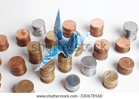 Origami crane made of brazilian money with piles of coins - stock photo